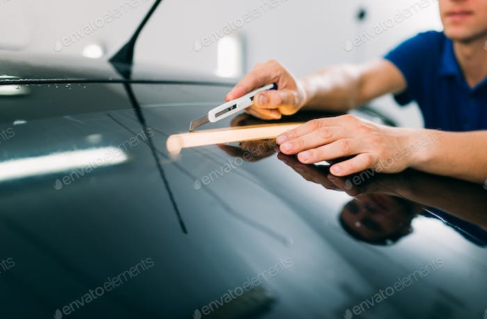 Worker with blade, car tinting film installation