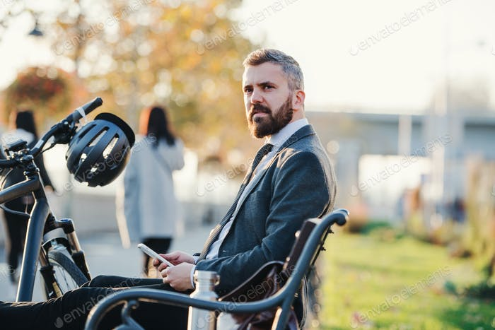 Businessman commuter with bicycle and smartphone sitting on bench in city.