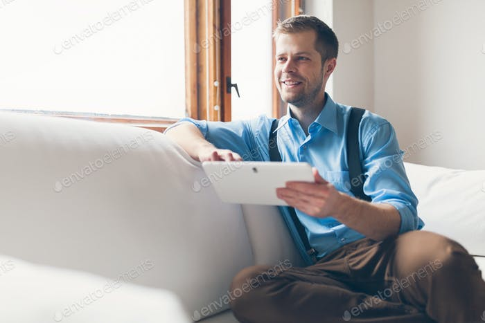 Handsome man sitting on sofa using a digital tablet