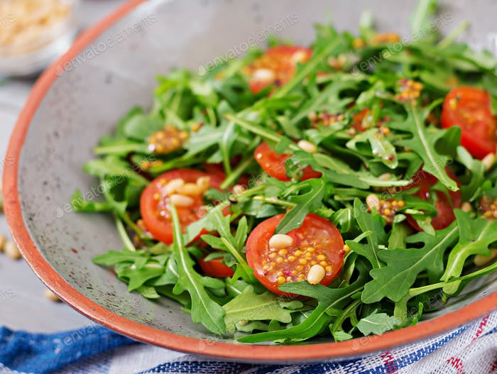 Dietary menu. Vegan cuisine. Healthy salad with arugula, tomatoes and pine nuts.