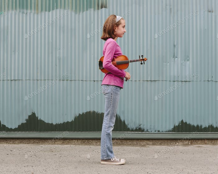 A ten year old girl holding a violin under her arm, standing on a street.