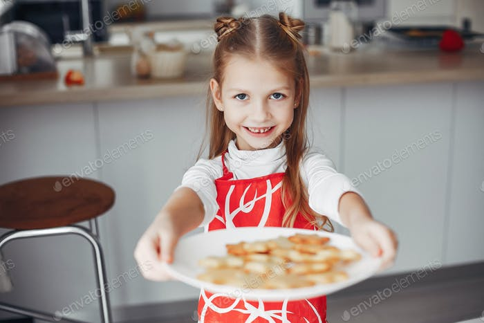 Little girl standing in a kitchen with cookies