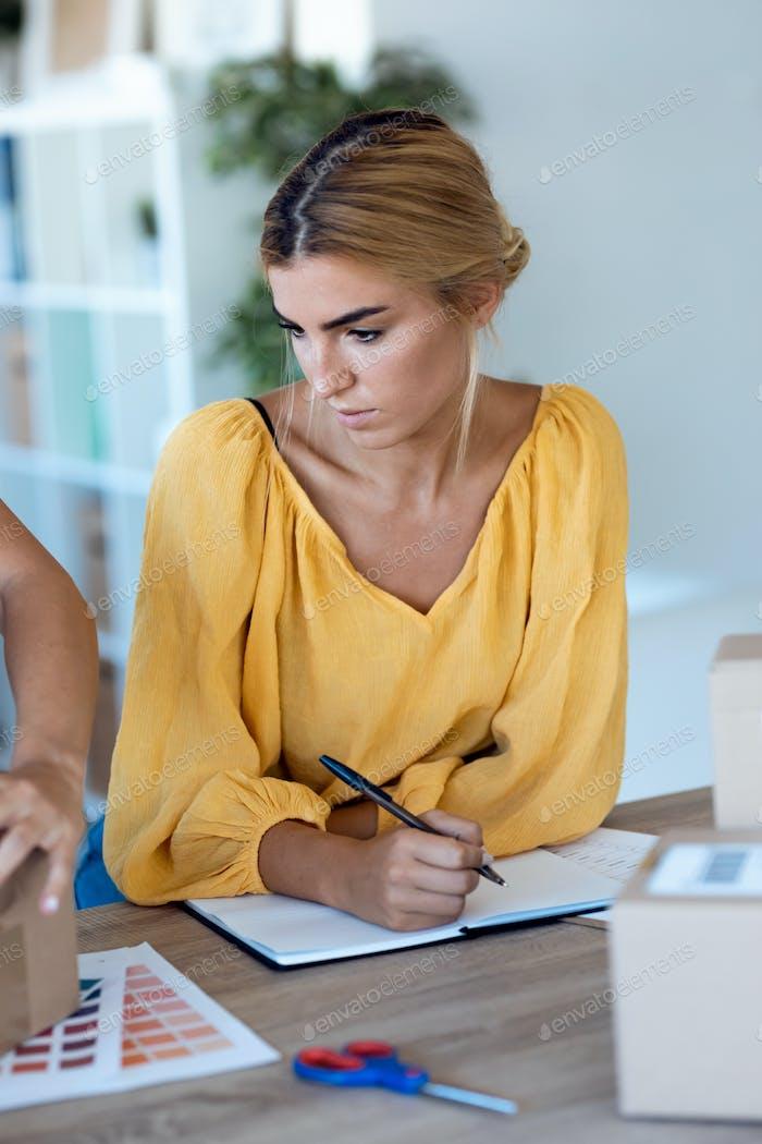красивая внештатная деловая женщина продавец проверяет заказ товара в ноутбуке