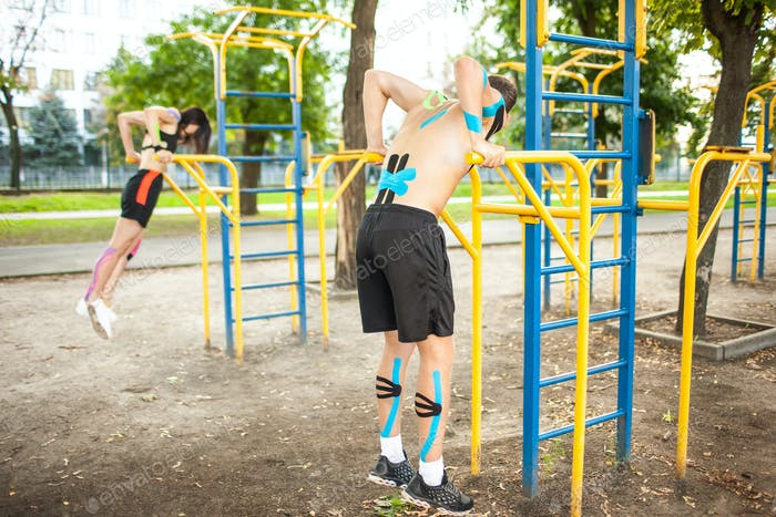 Couple with kinesiological taping working out at sports ground