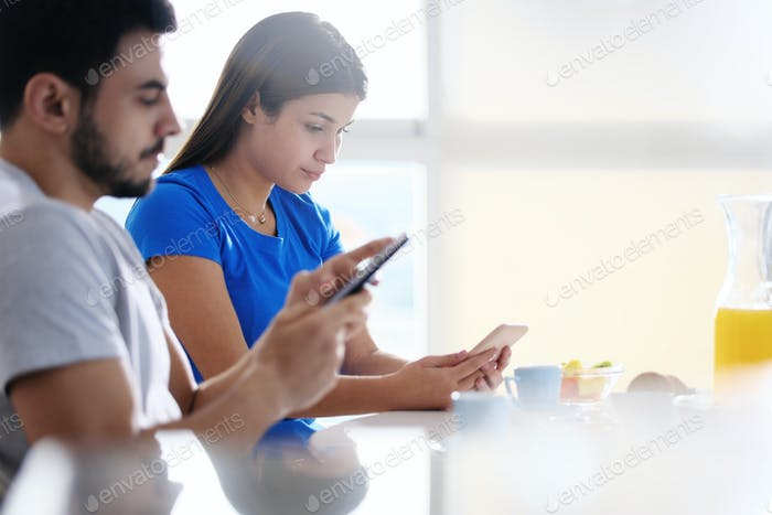Partners Using Phone While Eating Breakfast Together
