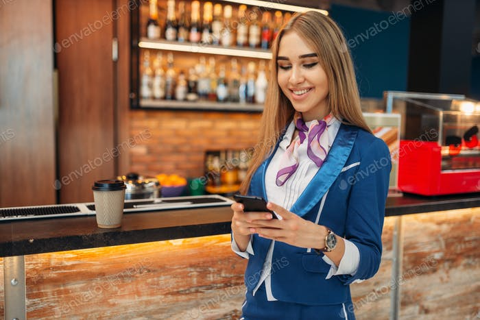 Stewardess using mobile phone in airport cafe