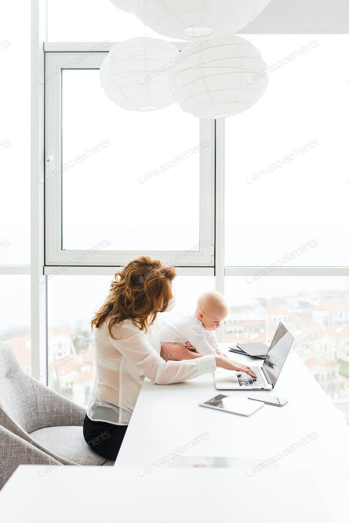 Schöne Business-Frau hält ihr niedlich kleines Baby während sitzen am Tisch arbeiten auf Laptop