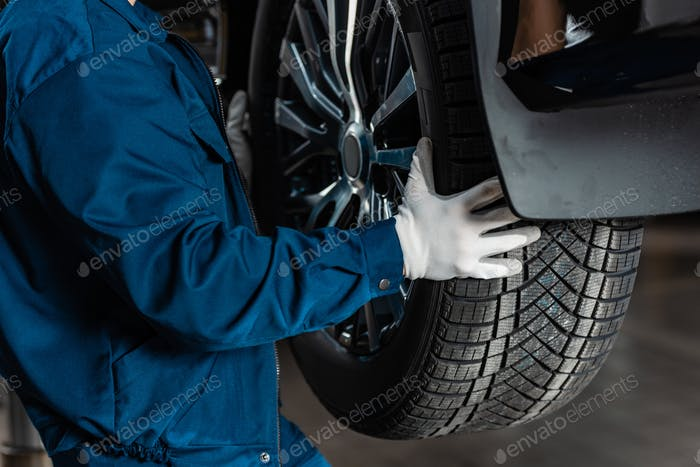 cropped view of mechanic installing new tire on car