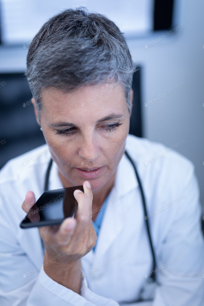 Close up of mature Caucasian female doctor talking on mobile phone in clinic at hospital