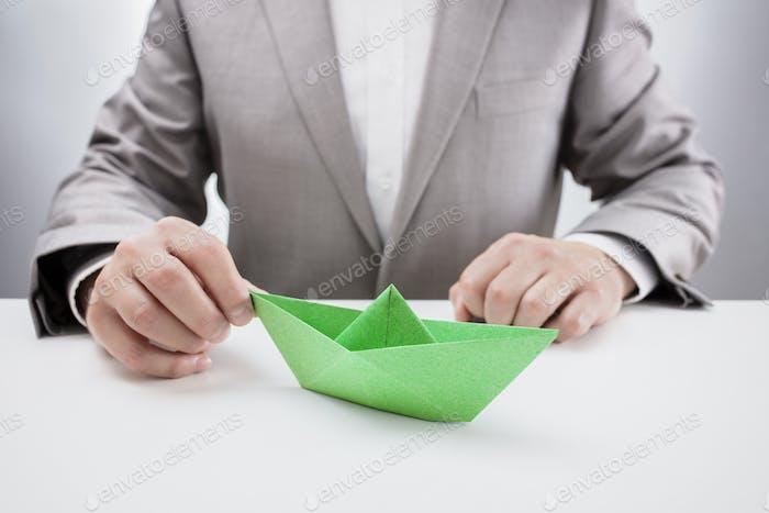 Geschäftsmann mit einem grünen Papierboot