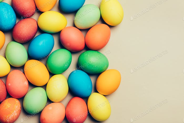 Couple of dyed eggs laying on a creamy background.