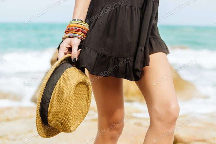 Niedliches Mädchen im schwarzen Sommerkleid an großen Steinen.