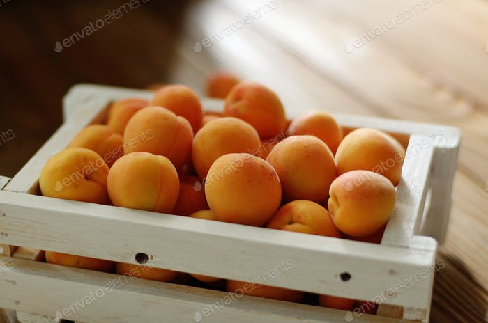 White wooden crate with apricots on table