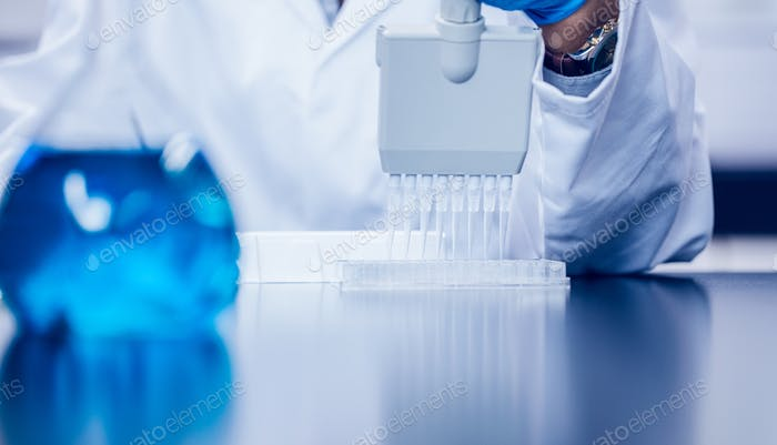 Science student using electronic pipette at the university