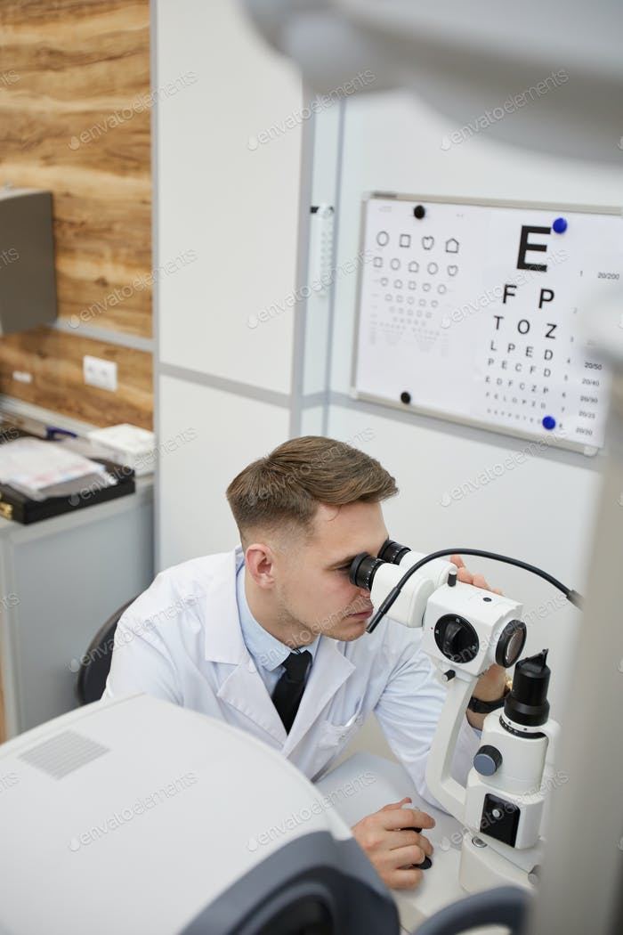 Optometrista masculino usando ecupment de prueba de visión