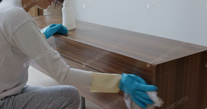 Woman clean the TV cabinet at home