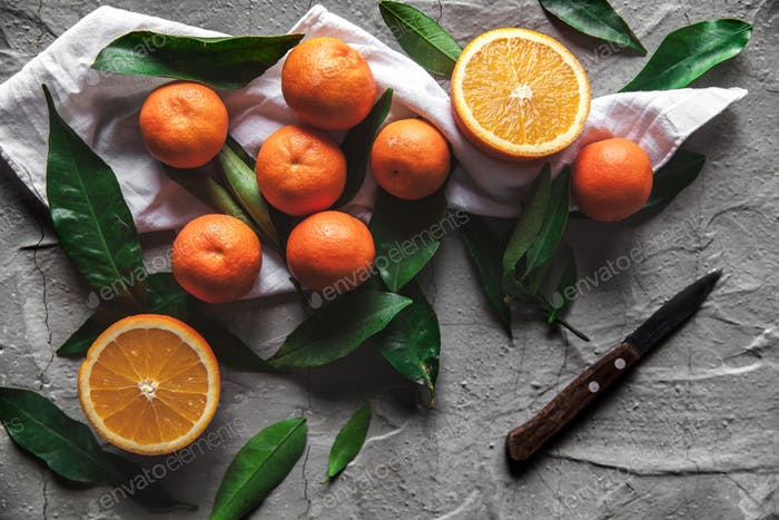 Citrus on table: mandarin, tangerine with a knife. Fresh organic juicy fruits