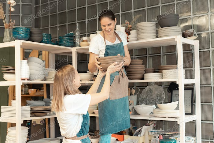 Woman with ceramic pottery. Attractive skilled young lady in apron standing at rack with dishes