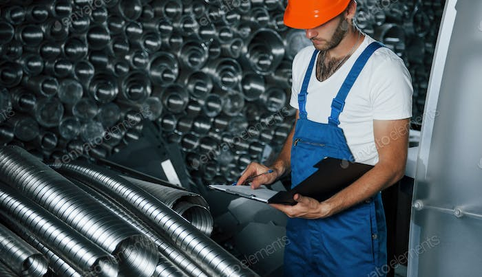 Many of ventilation pipes. Man in uniform works on the production. Industrial modern technology