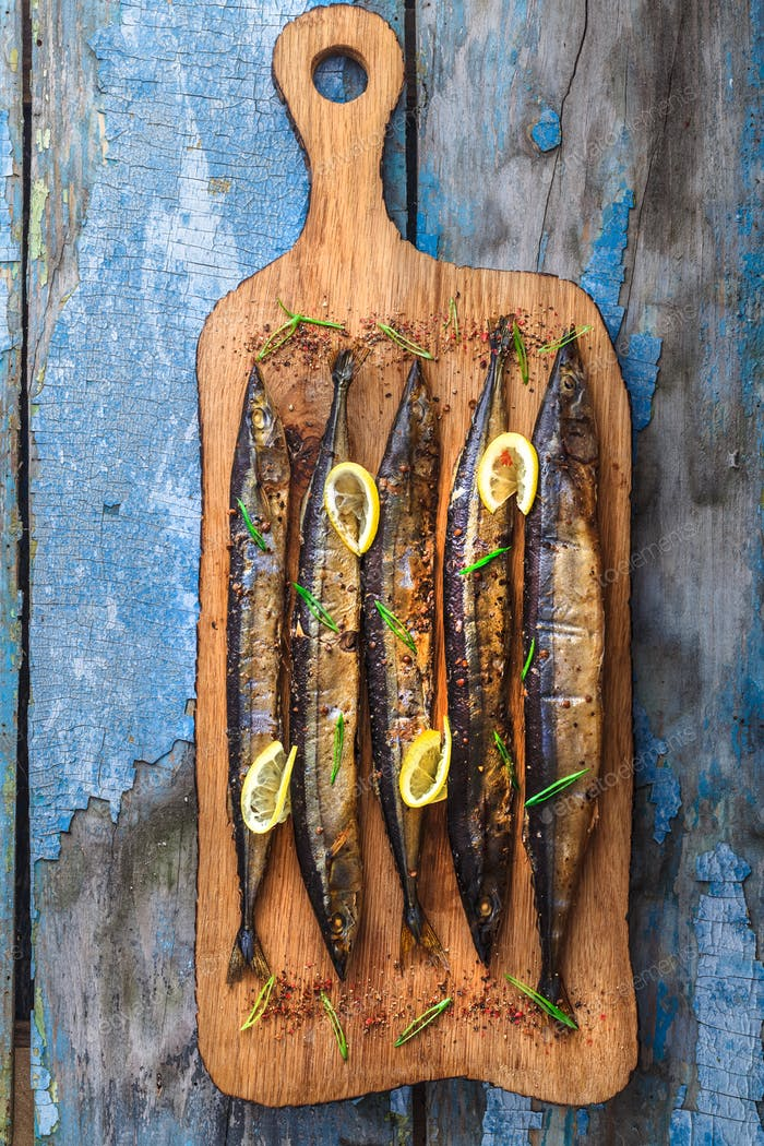 Smoked oceanic saury on wooden cutting board, top view, copy space