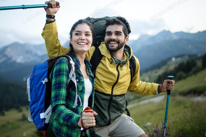 Couple - active hikers hiking enjoying view looking at mountain forest landscape