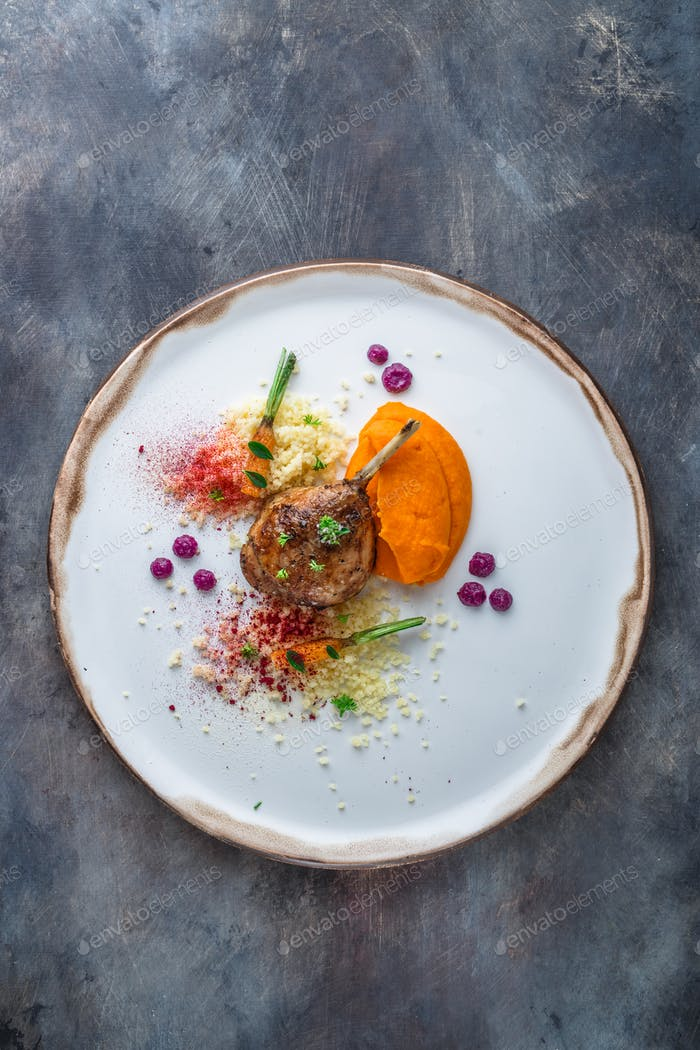 Duck leg confit with batat puree, carrots and couscous, restaurant meal, copy space