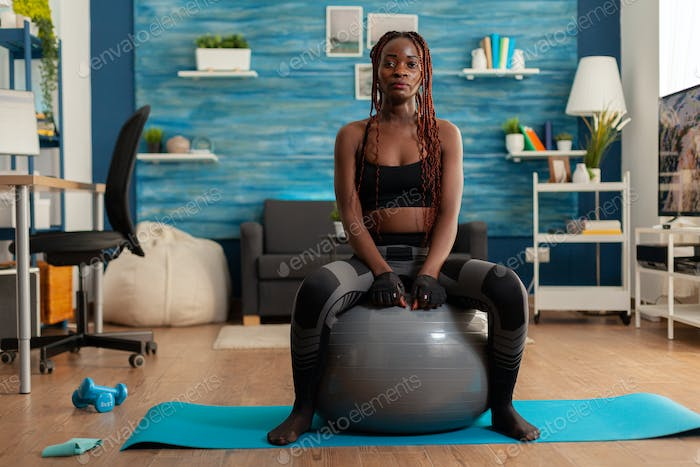 Sportive strong black woman sitting on stability ball