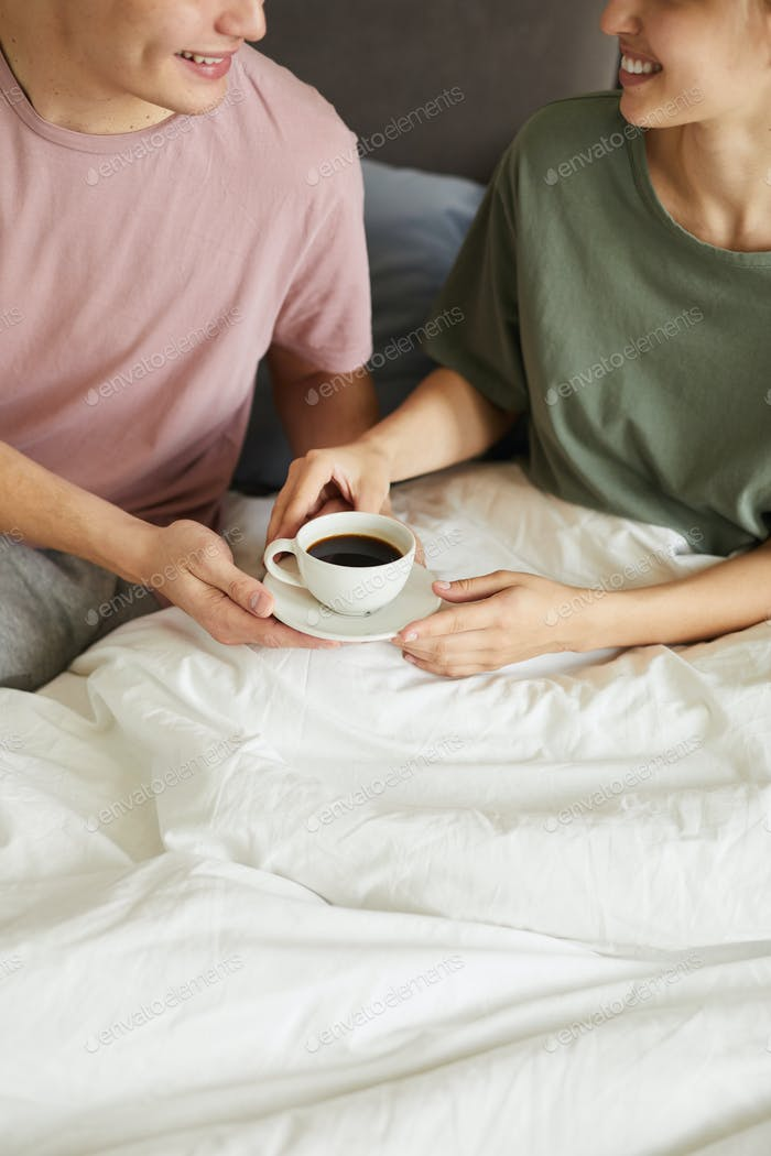 Happy young wife taking cup of coffee from husband