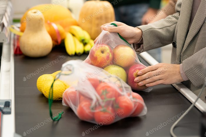 Hands of female consumer putting fresh apples and other products on counter