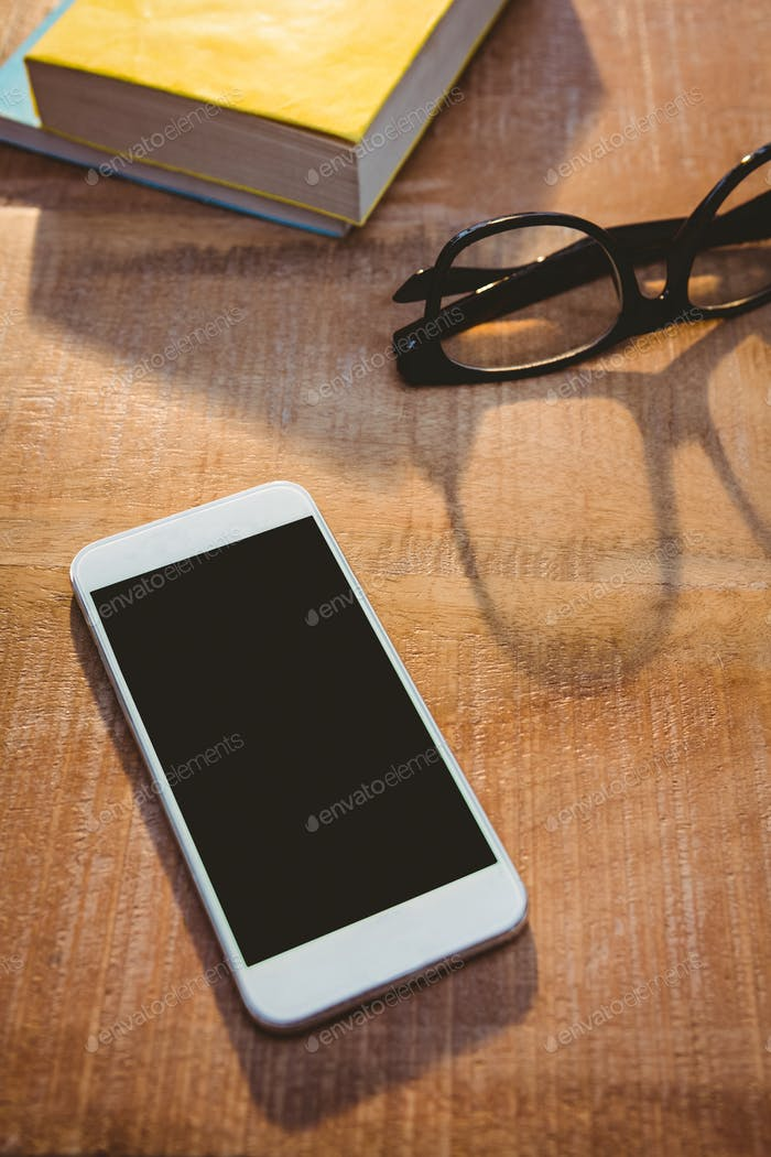 Close up view of smartphone and glasses on wood plank