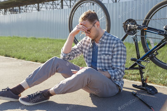 A puzzled man sitting on the road with brocken bicycle