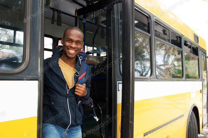happy young african american travel man with bag getting off bus