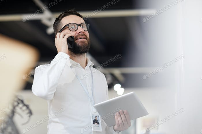 Bearded Manager Speaking by Phone in Art Gallery