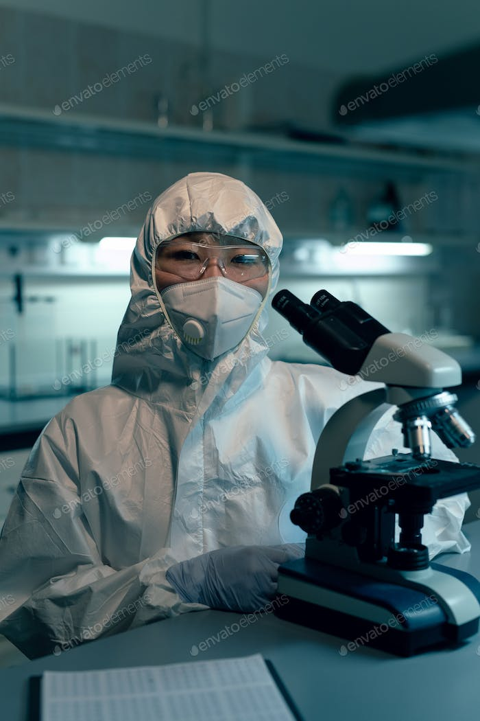 Female scientist in protective workwear looking at you