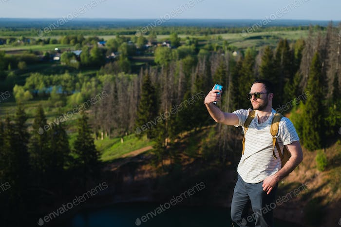 Young stylish man with a beard wearing sunglasses makes selfie on the canyon cliff