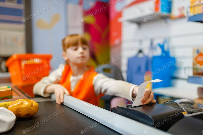 Cute girl at the register makes check for purchase