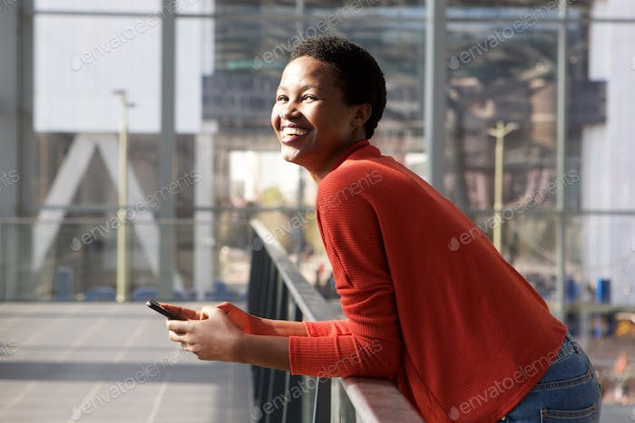 Side of happy young african woman laughing with cellphone