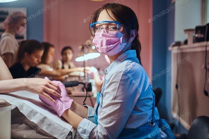 Young manicure master at her workplace working on woman's nails.