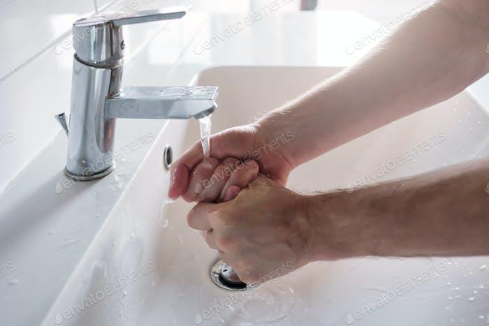 Caucasian man washing hands at home. Hygienic measure against coronavirus