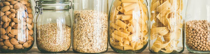 Uncooked cereals, grains, beans and pasta on table, wide composition