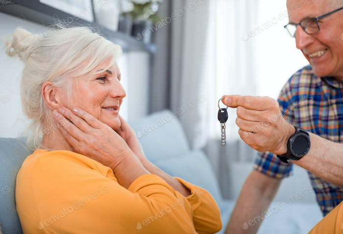 Senior husband giving keys of new house to his wife