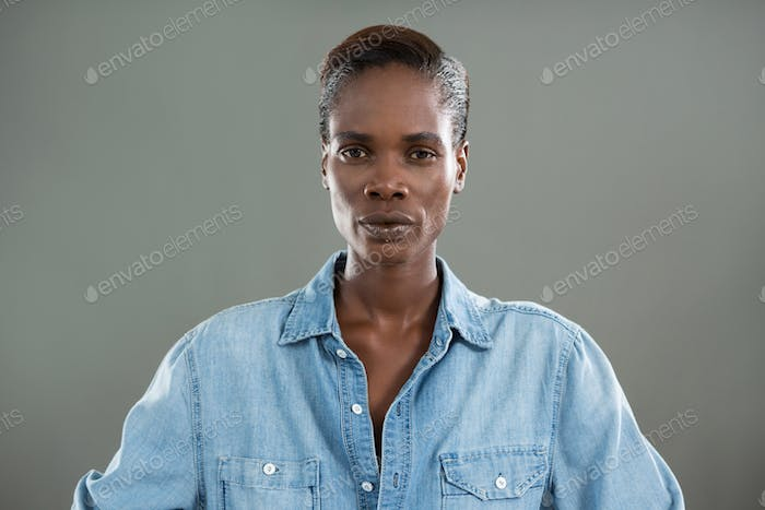Androgynous man in denim shirt posing against grey background