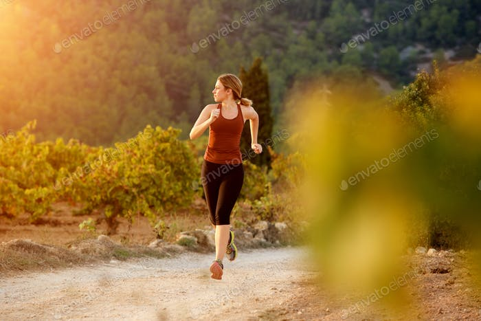 healthy young woman running on dirt road in countryside