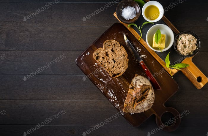 Tuna spread with fresh bread slice, sage butter, olive oil and salt on rustic wooden table