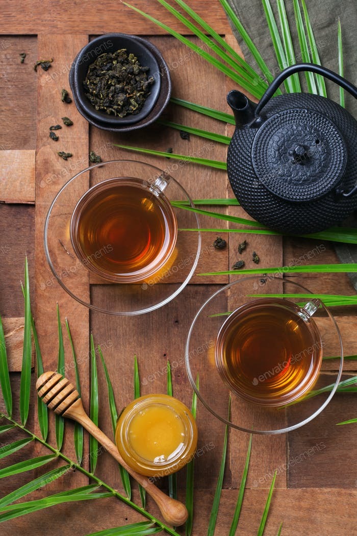 Cup of green tea and honey on a wooden table