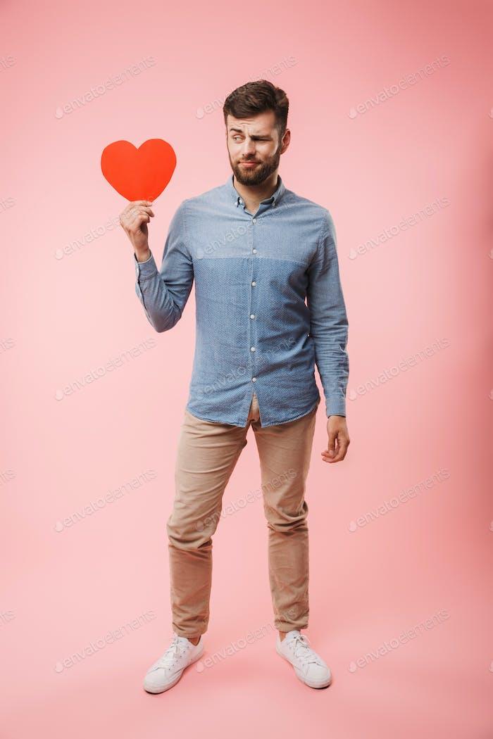 Volle Länge eines verwirrten jungen Mannes mit rotem Herz