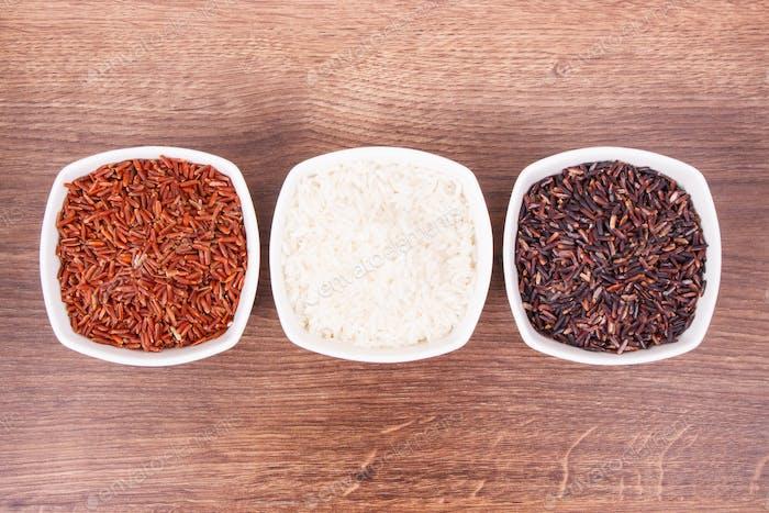 Weißer, roter und schwarzer Reis in Glasschale, gesundes Essen