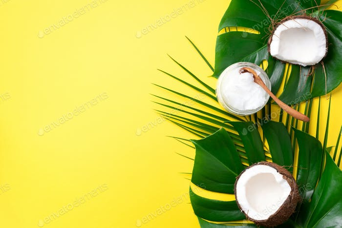 Coconut oil and ripe coconuts, tropical palm and monstera leaves on yellow background with copy