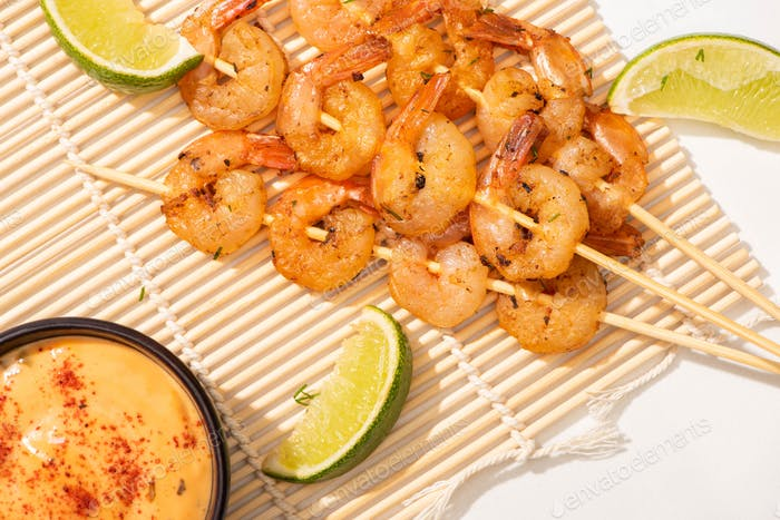 top view of prawns on skewers with lime and sauce on bamboo mat on white background