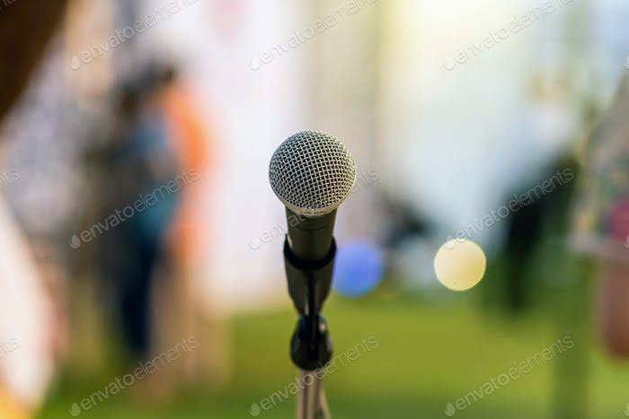 Microphone on the stage over the Abstract blurred photo of green grass